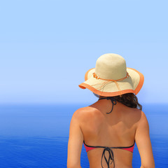 Woman in bikini and hat overlooking the seascape