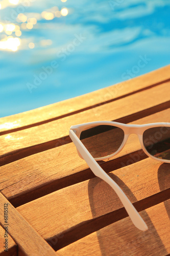 Sunglasses on wooden planks and water on sunset - 68115512