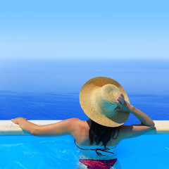 Woman in hat overlooking the seascape from the poolside