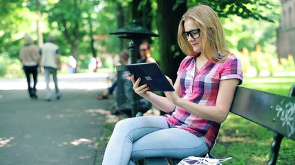 Young teenager with tablet computer sitting on bench in park