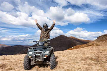 male rider on ATV at mountain top