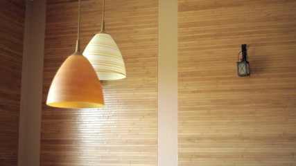 two beautiful chandeliers on the background of wooden wall