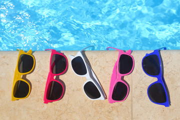 Colorful sunglasses in the row by the poolside