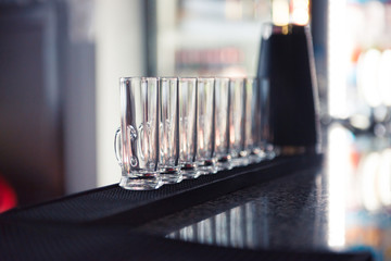 Row of glass shots at bar