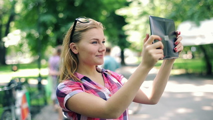 Young teenager taking photos with tablet computer in city park
