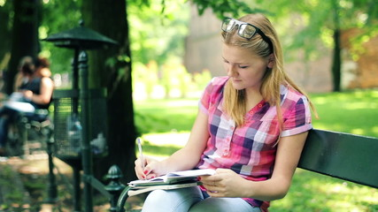 Young teenager doing homework on bench in city park