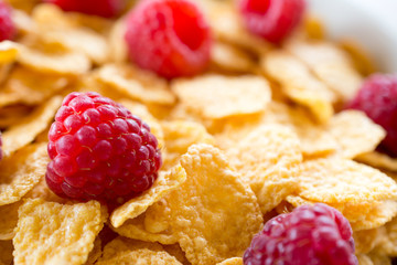 Cornflakes and red rasberries in a white bowl