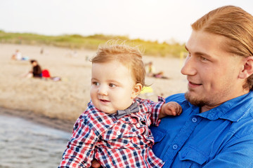 Young father holding his child on the beach having fun together.