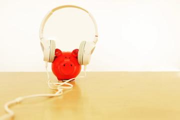 rotes Sparschwein mit Kopfhörer