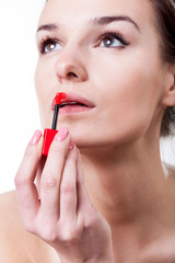 Woman painting her lips with red lipstick