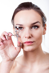 Beautiful girl using eyelash curler