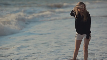 Girl with long blond hair walking along the seashore