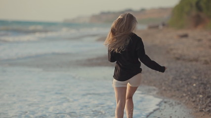 Beautiful girl with long blond hair running along the sea shore