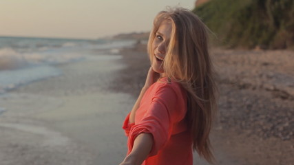 Young blond girl with long hair in red blouse on the beach