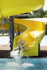 Children slide down a water slide