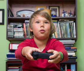 Boy teenager with  playing a video game console.