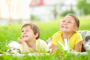 Little girl and boy are playing outdoors