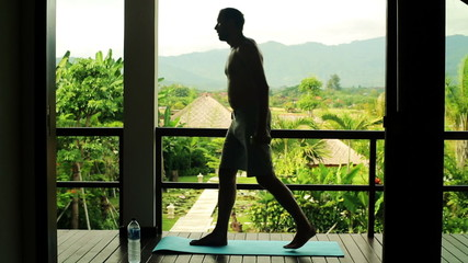 Silhouette of man exercising on terrace of country house