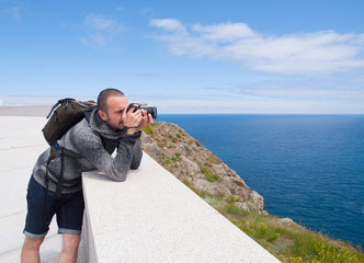 Photographer sightseeing and photographing a beautiful coastal l
