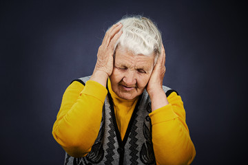 Stressed depressed elderly woman, isolated on black background