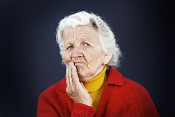 Skeptical old elderly woman isolated on dark black background