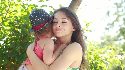 Beautiful happy mother embracing her kid on summer background