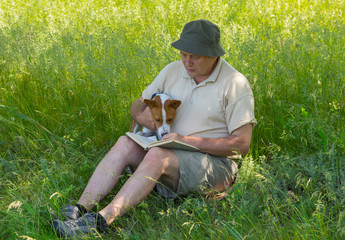 Mature man and young dog reading interesting book