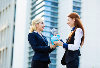 Banking concept. Business women deposit money in piggy bank