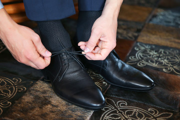 Businessman putting on black leather shoes for work.