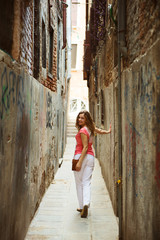 Pretty woman in narrow Venice street