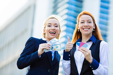Happy business women holding credit cards, cash reward