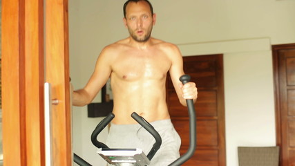 Young man exercising on elliptical trainer at home