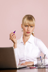 Serious office woman at desk listening attentively
