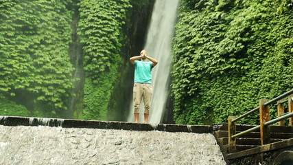 Man meditating by amazing waterfall, Bali, Indonesia