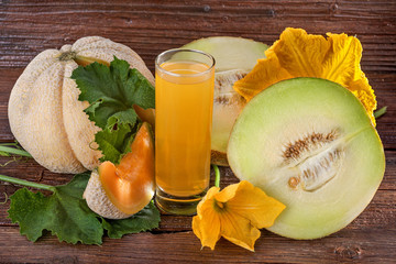 Cantaloupe melon with juice on a wooden background