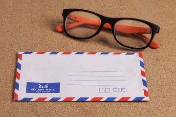 envelope and glasses wooden background.