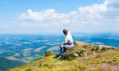 Man sitting and looking at mountains