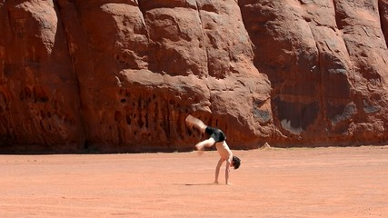 Boy dancing breakdance in the famous Monument Valley USA