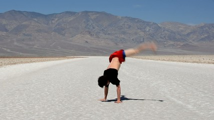 Boy dancing breakdance in the famous Death Valley USA