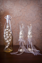 Decorated wedding glasses and bottle of champagne