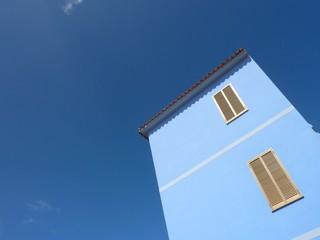 facciata di edificio azzurro con finestre chiuse