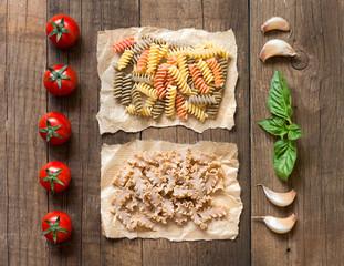 Pasta, pomodori, aglio e basilico sopra il tavolo di legno