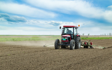Young farmer sowing crops at field with pneumatic sowing machine