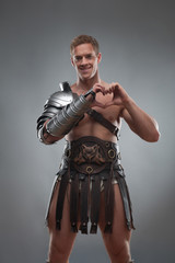 Gladiator in armour showing heart sign over grey background