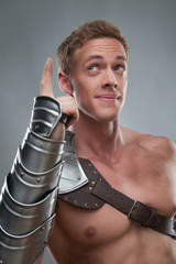Gladiator in armour pointing at something over grey background