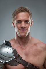 Closeup portrait of Gladiator in armour over grey background