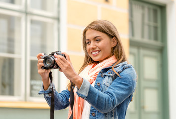 smiling girl with digiral photocamera in the city