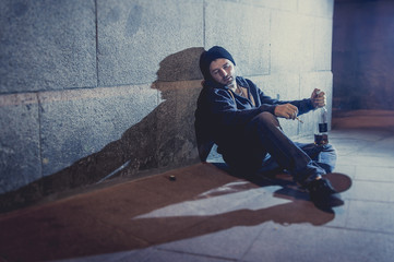 alcoholic drunk man sitting on street drinking alcohol