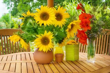 Sonnenblumen und Gladiolen auf Gartentisch