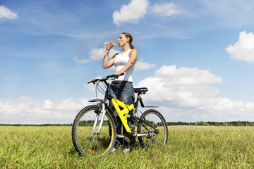 Biker woman , drinking on a meadow